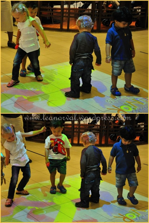 some children dancing on the floor. they were actly trying to step on the colourful 'shadow' on the floor which moved around that square...